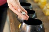 Młody dorosły kobieta oddania jej pieniądze w świątyni — Zdjęcie stockowe