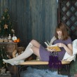 Young girl in a New Years interior reading a book — Stock Photo #59556533