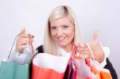 Portrait of a blond woman with shopping bags in a studio — Stock Photo