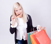 Portrait of a blond woman with shopping bags in a studio — Stockfoto