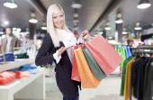 Smiling young blond woman in clothing store  — Stok fotoğraf