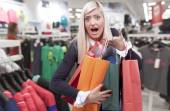 Smiling young blond woman in clothing store  — 图库照片