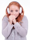 Beautiful redhead woman wearing white earmuffs — Stock Photo