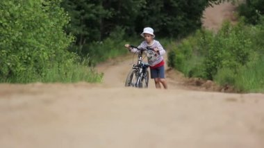 Boy goes along with the bike on a country road — Stock Video