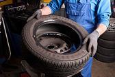 Mecânica reparos um pneu na garagem. — Fotografia Stock