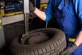 Mechanical repairs a tire in the garage. — Stock Photo