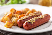 Sausages and potatoes on plate — Stock Photo