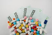 Medicines, tablets on the banknotes of 100 euros — Stock Photo