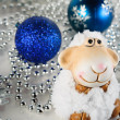Toy sheep on the background of Christmas decorations — Stock Photo #60546919