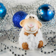 Toy sheep on the background of Christmas decorations — Stock Photo #60547091