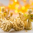 Six straw christmas balls and two angels on white background with blurred yellow christmas lights — Stock Photo #55270005
