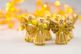 Six straw christmas angels on white background with blurred yellow christmas lights — Stock Photo