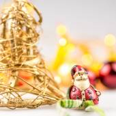 One straw christmas bell and one ceramic santa claus on white background with blurred yellow christmas lights — Stock Photo