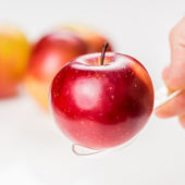 Hand is holding red apple on translucent medicine spoon on the  table symbolising that drinking and eating of apple products prevents diseases and is full of vitamins, other apples at background — Stock Photo