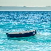 Little blue boat is seesawing on waves in mediterrean   — Stock Photo