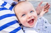 Baby boy is smiling broadly while holding his father's hand in a park in summer time — Stock Photo