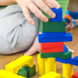 Child is playing with multicolored cubes on wooden floor — Stock Photo #57937323