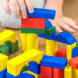 Child is playing with multicolored cubes on wooden floor — Stock Photo #57937325