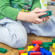 Child is playing with multicolored cubes on wooden floor — Stock Photo #57937327