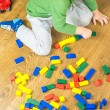 Child is playing with multicolored cubes on wooden floor — Stock Photo #57937337