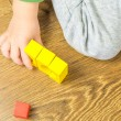 Child is playing with multicolored cubes on wooden floor — Stock Photo #57937413