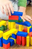 Child is playing with multicolored cubes on wooden floor — Stock Photo