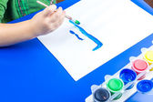 Child is painting a picture with tempera paints on blue table — Стоковое фото