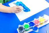 Child is painting a picture with tempera paints on blue table — Stock Photo