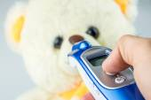 Measuring temperature with tele thermometer of baby teddy bear — Stock Photo