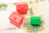 Three little houses made of plastic are laying on one yuan banknote — Stock Photo