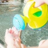 Child is playing with a watering can in an indoor baby pool — Stock Photo