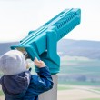 Young boy is looking through a telescope — Stock Photo #70243693