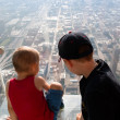 Boys looking down at city from skyscarper — Stock Photo #55899511