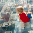 Boy looking down at city from skyscarper — Stock Photo #55930583