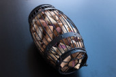 Cork cage filled with corks lies on black surface  — Stock Photo