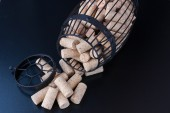 Cork cage filled with blank wine corks lies on wooden surface  — Stock Photo