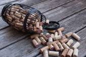 Cork cage filled with corks lies on wooden surface  — Stock Photo
