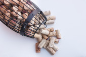 Cork cage filled with wine corks lies on white surface  — Stock Photo