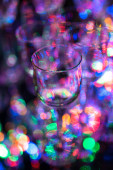 Small crystal liqueur glass on background of colorful lights - v — Stock Photo