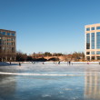 Ice skating rink on a frozen lake between office buildings — Stock Photo #62831055