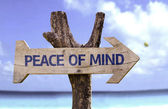 Peace of Mind wooden sign with a beach on background — Stock Photo