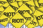 Riot! written on multiple road sign — Stock Photo