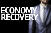 Economy Recovery written on a board with a business man — Stock Photo