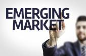 Business man pointing to transparent board with text: Emerging Market — Stock Photo
