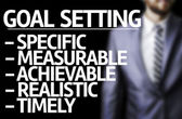 Description of Goal Setting written on a board with a business man — Stock Photo