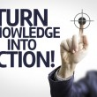Business man pointing the text: Turn Knowledge Into Action! — Stock Photo #54628801