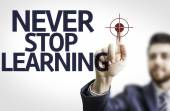 Business man pointing the text: Never Stop Learning — Stock Photo