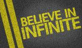 Believe in Infinite written on road — Stock Photo