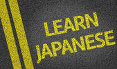Learn Japanese written on the road — Stock Photo