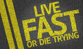 Live Fast or Die Trying written on the road — Stock Photo